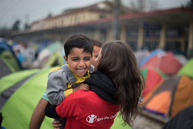 A Save the Children member holds a smiling child in arms